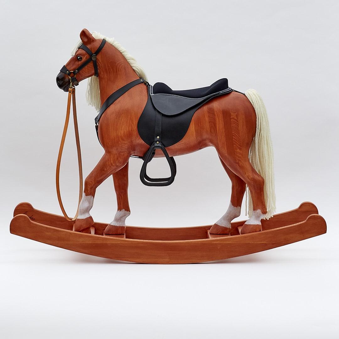 Le cheval à Bascule en Bois grand Royal Spinel de couleur alezan est équipé d'un harnais de cuir et d'une selle.