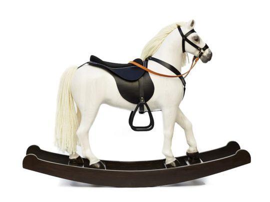Le cheval à Bascule en Bois grand Čenda 53 de couleur blanc est équipé d'un harnais de cuir et d'une selle